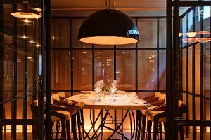 Illuminated dining table and chairs in glazed booth