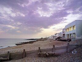 Seashore below cloudy sky, pebbly beach and modern beach houses