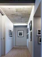 Illuminated hallway with gallery of black and white photos below exposed concrete ceiling