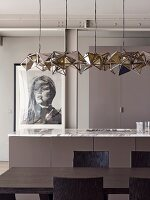 Designer pendant lamp above dark brown dining table and kitchen counter with marble worksurface; framed photographic portrait of woman