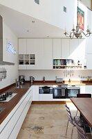 Küchenzeile übereck mit Holz Arbeitsplatte, im Hintergrund eingebauter Oberschrank mit Öffnungen unter Galerie