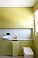 Bad mit grünen Einbauschränken und weisser Waschschüssel