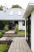 Terrassen und Wege mit Holzdielenbelag vor modernem Wohnhaus