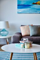 Round retro coffee table in front of sofa with scatter cushions and table lamp on side table below painting on wall