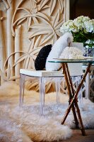 White coral on side table with wooden legs next to chair with plexiglas frame on flokati rug