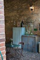Vintage furnishings on gravel floor in rustic surroundings