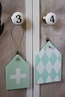 Shabby chic pendants with diamond and cross motifs hung from furniture knobs