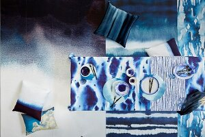 Rugs, cushions, tablecloth and crockery in blue watercolour patterns