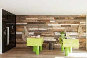 Custom kitchen counter and breakfast bar on pillars painted lime green against vintage wooden-board cladding on wall