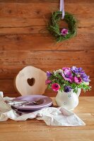 Bouquet of anemones in rustic milk jug and stacked plates on table