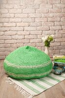 Crocheted green pouffe on green and white rug
