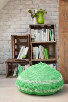 Crocheted, green pouffe in front of bookcase made from stacked wooden crates