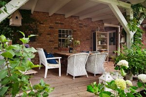 White wicker furniture and garden bench on pleasant wooden terrace against brick façade
