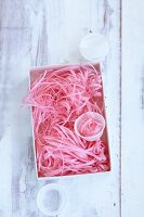 Strips of pink silk paper in a box as decoration