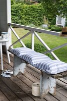 A bench on a terrace with a homemade, striped cushion