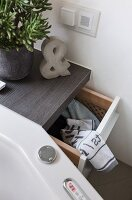 A custom-made cupboard with a pull-out laundry basket