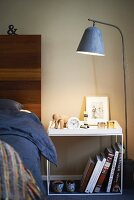Standard lamp next to delicate bedside table