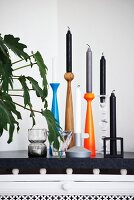 Black, white and grey candles in candlesticks