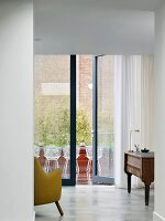 Study with view through glass wall onto terrace with classic wire mesh chairs