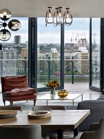 Seating area with coffee table next to glass wall with view of London; dining table in foreground