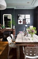 White chairs with perforated backrests around rustic wooden table in dining room with black-painted walls and white stucco ceiling
