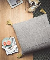 A homemade floor cushion knitted from grey woollen yarn