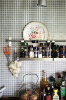 Spice rack hung from rail on pale grey mosaic wall tiles in kitchen