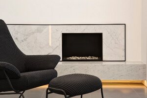 Elegant, modern, marble-clad fireplace with indirect lighting and designer armchair