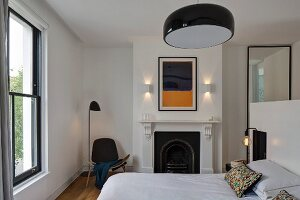 Modern bedroom with designer furniture, traditional fireplace and minimalist ambiance