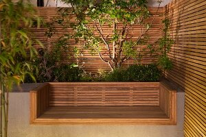 Custom, modern concrete bench with wooden seat, integrated raised bed and wooden screens
