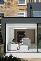 Modern, dark grey extension to Georgian terrace house with open, sliding glass wall leading to garden; woman reading on pale grey sofa