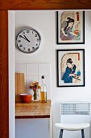 Framed Japanese artworks next to clock on kitchen wall
