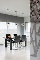 Black dining set on white, tiled floor below shiny, silver pendant lamps in designer interior