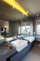 Bathroom with mirrored wall, white twin sinks on dark-grey washstand counter and yellow light strip