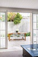 Blick durch offene Terrassentür auf Essplatz im Freien vor weissem Lattenzaun