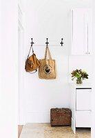 Nostalgische Wandhakenleiste mit aufgehängten Taschen neben weissem Schrank