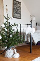 Small Christmas tree and gnomes at foot of metal bed