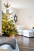Lights on Christmas tree in living room with Star of David on wall