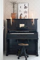Old black piano lit by candles