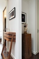 Custom walnut console table below framed picture and Madonna figurine on wooden plinth in niche