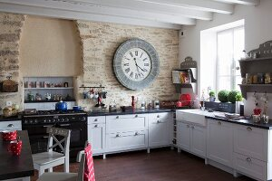 White country-house kitchen with large clock on stone wall