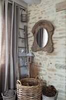 Wicker baskets of pine cones and firewood in corner below rustic mirror on stone wall