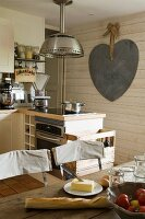 Breakfast ingredients on table in rustic fitted kitchen with large heart-shaped decoration on wall