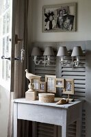 Grey wooden table below sconce lamps hung on panelling made from old window shutters
