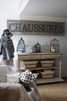 Armchair covered in throw, antique-style console table, tailors' dummy wearing hat and coat and vintage sign on wall
