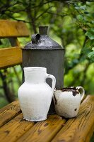 Vintage-style, still-life arrangement of white jugs and canister on wooden bench in garden