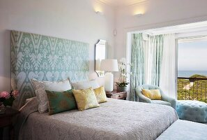 Bed with upholstered headboard in bedroom with sea view