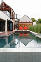Modern house with pool, steel spiral staircase and orange loungers against stone wall
