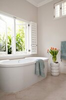Free-standing bathtub in minimalist bathroom with white shutters and walls painted beige