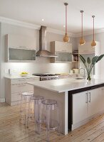 Pale, fitted kitchen with modern island counter and plexiglas bar stools